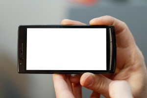 Close up of a mobile phone with a touch screen. Focus is on the phone with small DOF.